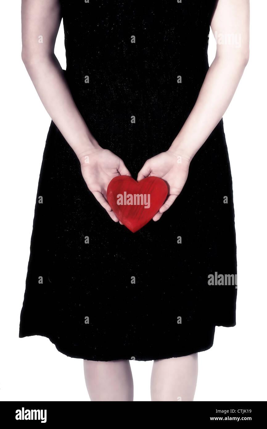 eine Frau in einem schwarzen Kleid mit einem roten Herzen hinter ihrem Rücken Stockbild