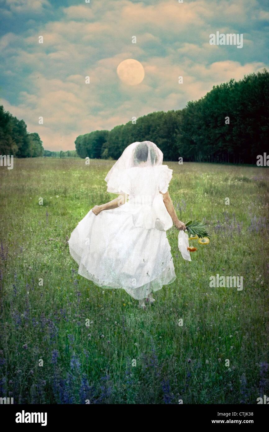 eine Frau läuft mit einem Brautkleid in einem Feld von Blumen Stockbild