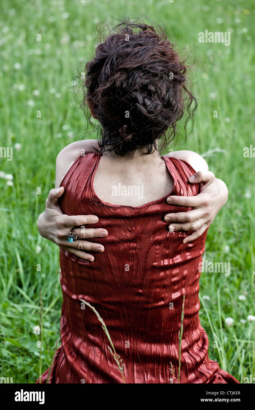 eine Frau sitzt auf einer Wiese, umarmen sich Stockbild