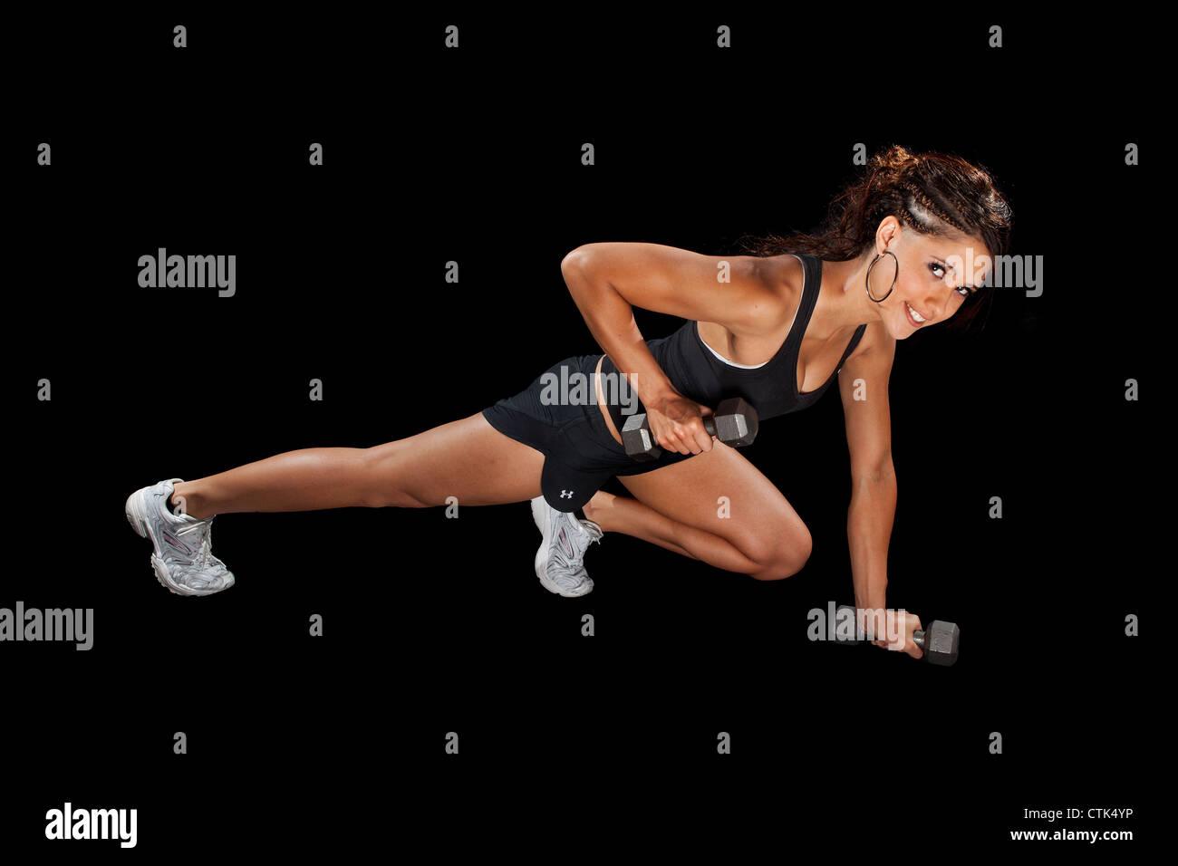Ausübung Fitness Tänzer dabei drücken sich Übung mit Gewichten Sport Modell vor schwarzem Hintergrund Studiobeleuchtung. Stockfoto