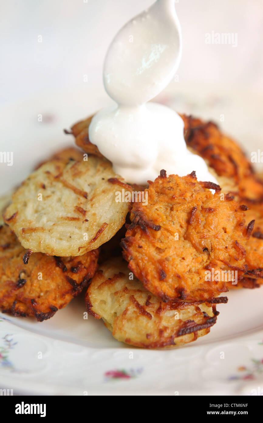 Kartoffelpuffer (Jiddisch: Latkes oder Latkas) traditionell gegessen während Chanukkah mit Soar Creme Stockbild