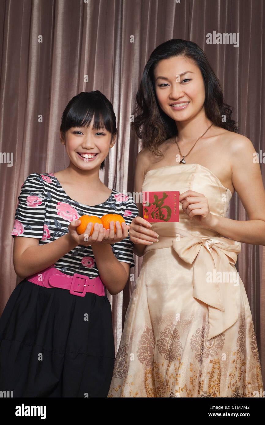 Porträt von fröhlichen Mutter und Tochter mit Mandarin-Orangen und ...