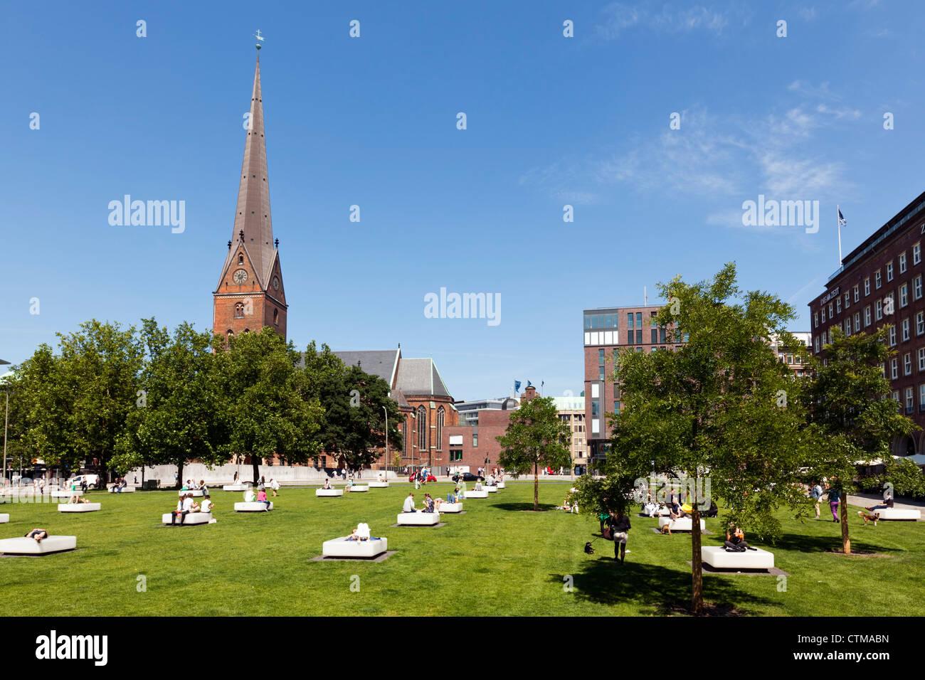 Domplatz-Platz und Kirche Petrikirche, Hamburg. Menschen, die genießen ihr Mittagessen brechen auf dem Rasen. Stockbild