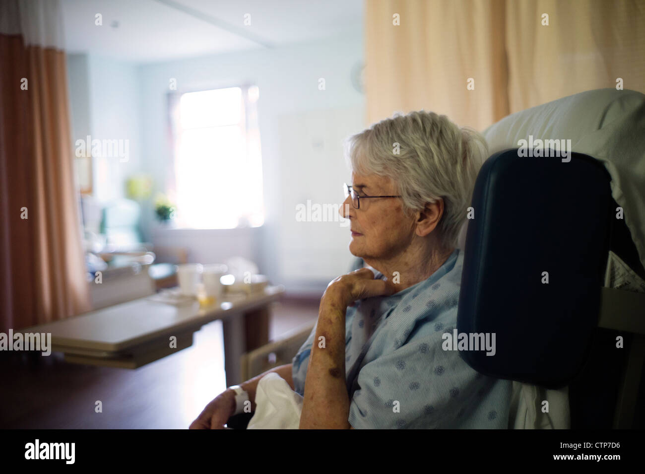 Alte Frau sitzt im Rollstuhl im Krankenhaus. Stockfoto