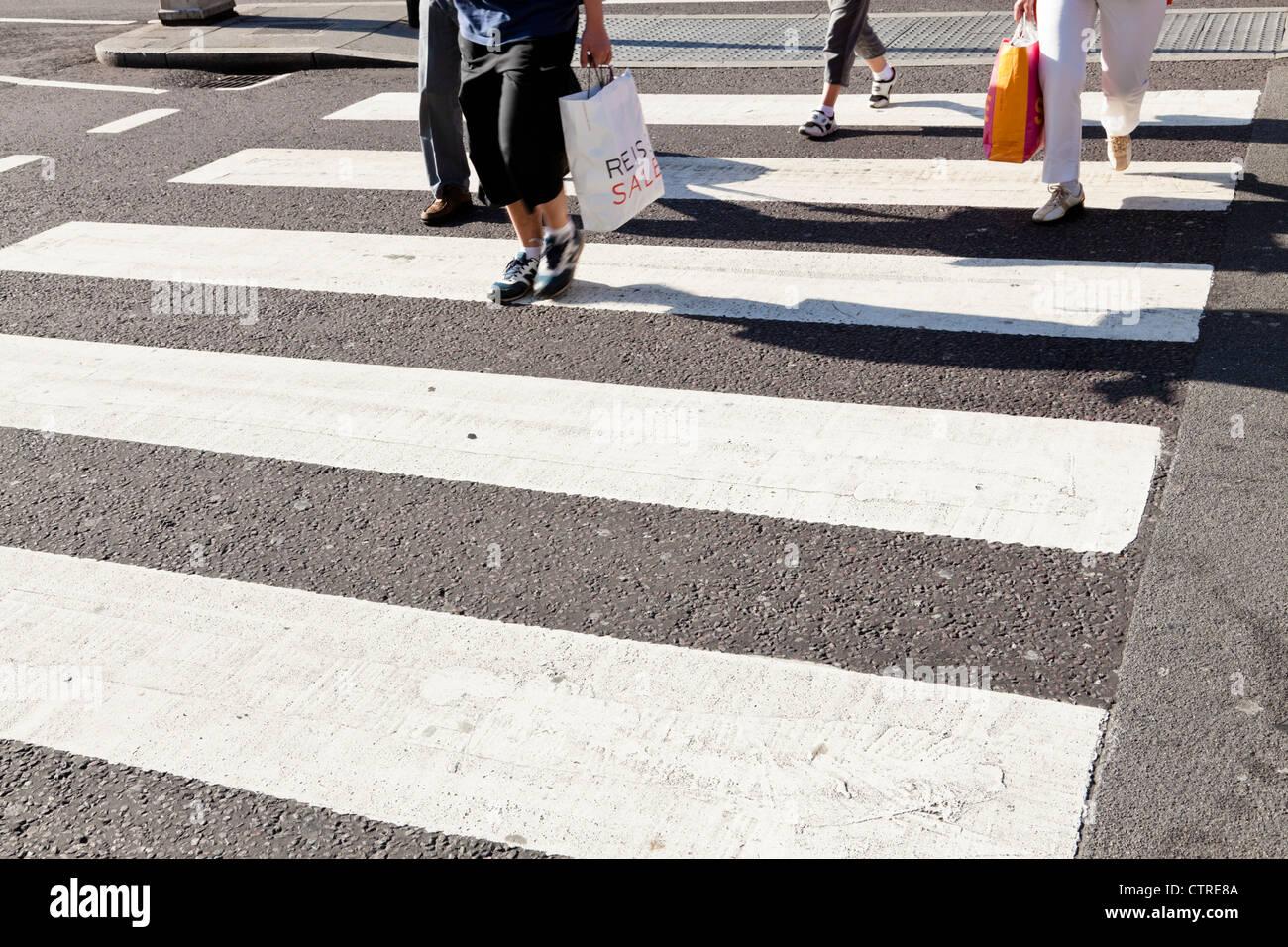 Menschen beim Überqueren der Straße an einem Zebrastreifen, England, UK Stockbild