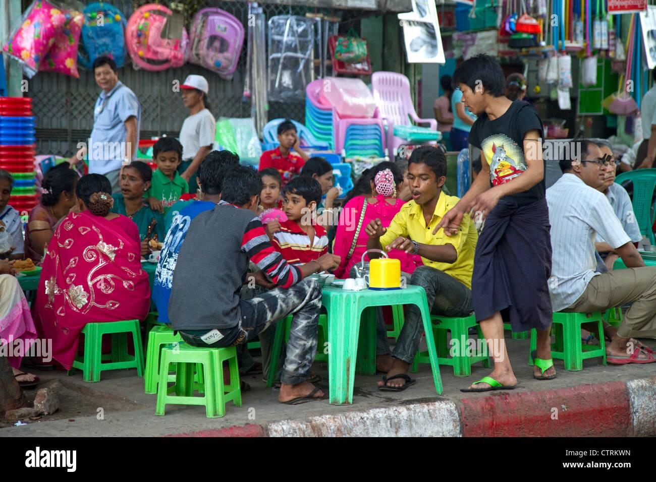Birmanische Menschen Essen und trinken an kleinen Tischen und Stühlen im Freien in Yangon (Rangoon), Myanmar Stockbild