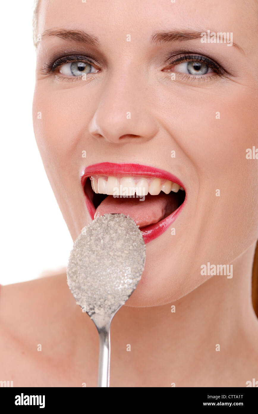 Frau lecken Weißzucker aus einem Löffel Stockbild