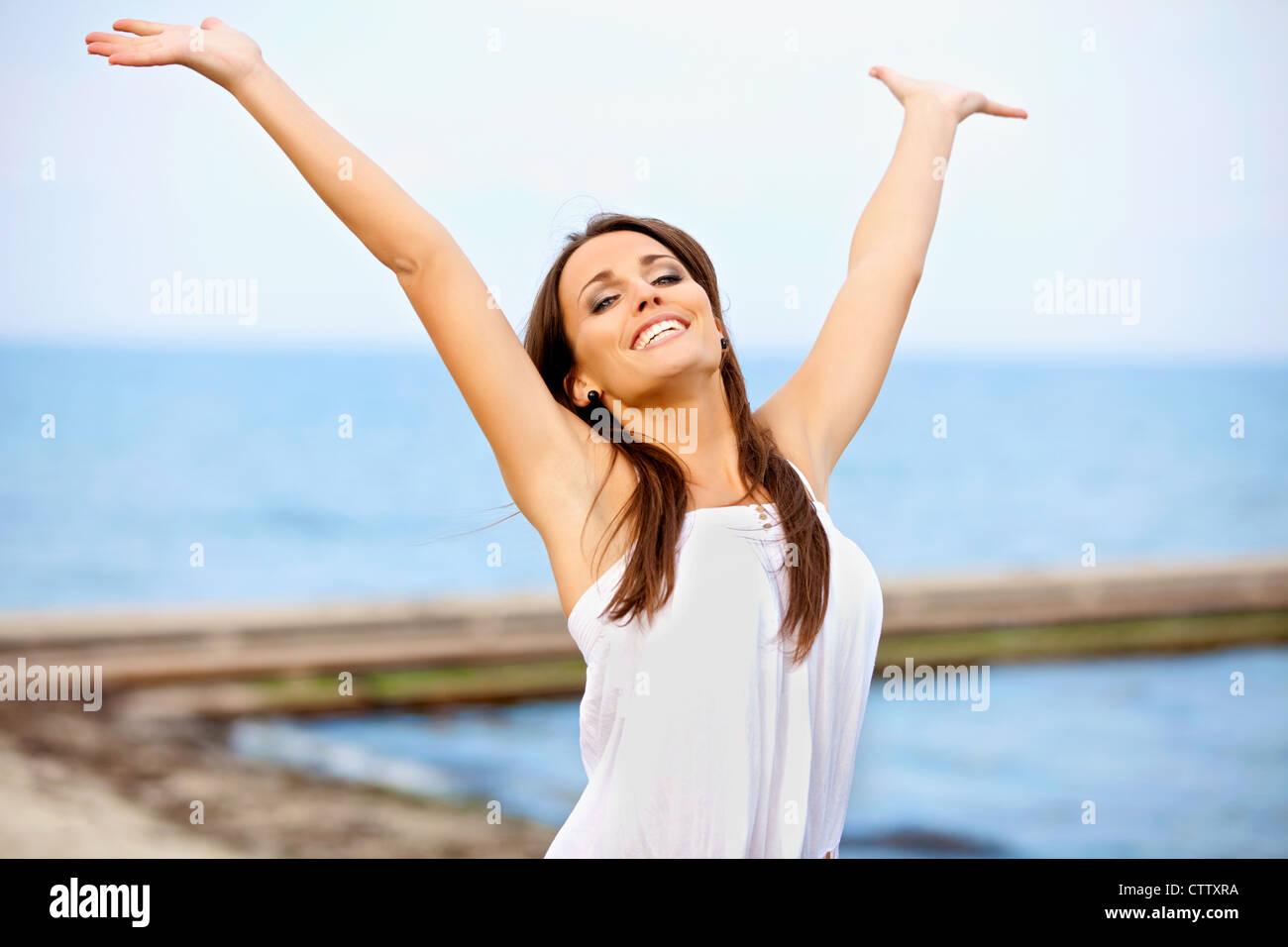 Fröhliche Frau mit über den Kopf erhobenen Armen Stockbild