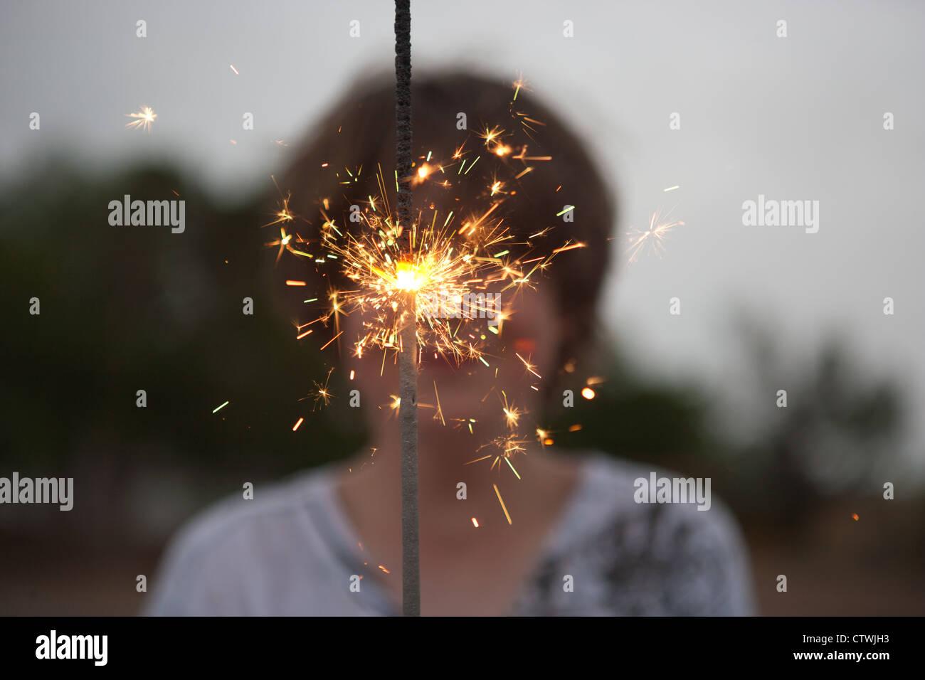 13 Jahre alter Junge hält eine große Spakler am 4. Juli. Stockbild