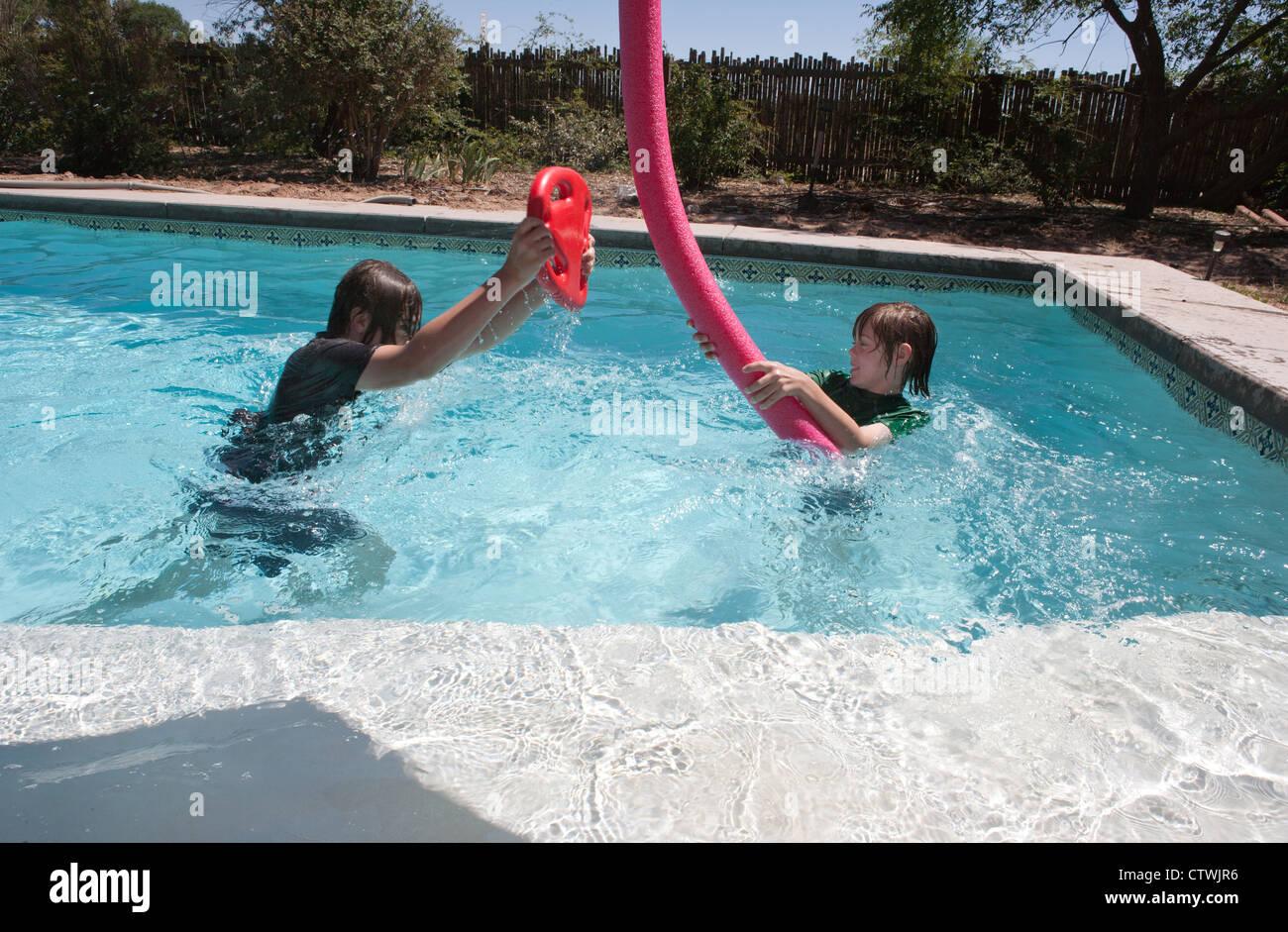 zwei jungen spielen k mpfen in einem pool mit floating nudel und kick board stockfoto bild. Black Bedroom Furniture Sets. Home Design Ideas