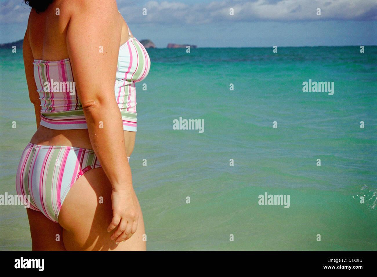 Ein Womans Torso stehend auf einem hawaiianischen Strand. Stockbild
