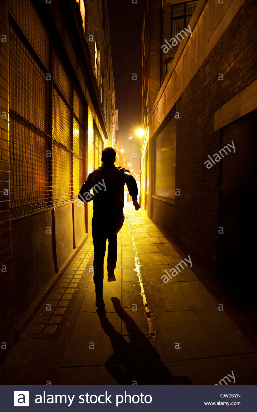Mann läuft durch eine Gasse in der Nacht Stockbild