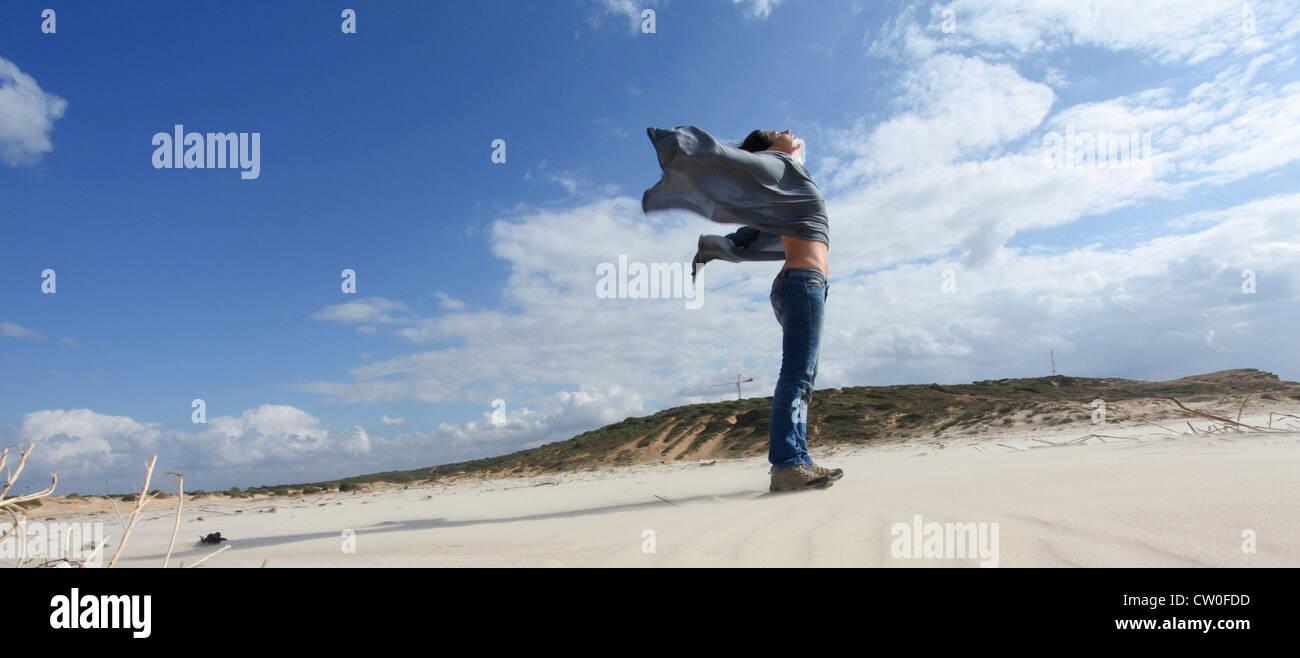 Frau stehend auf windiger Strand Stockbild