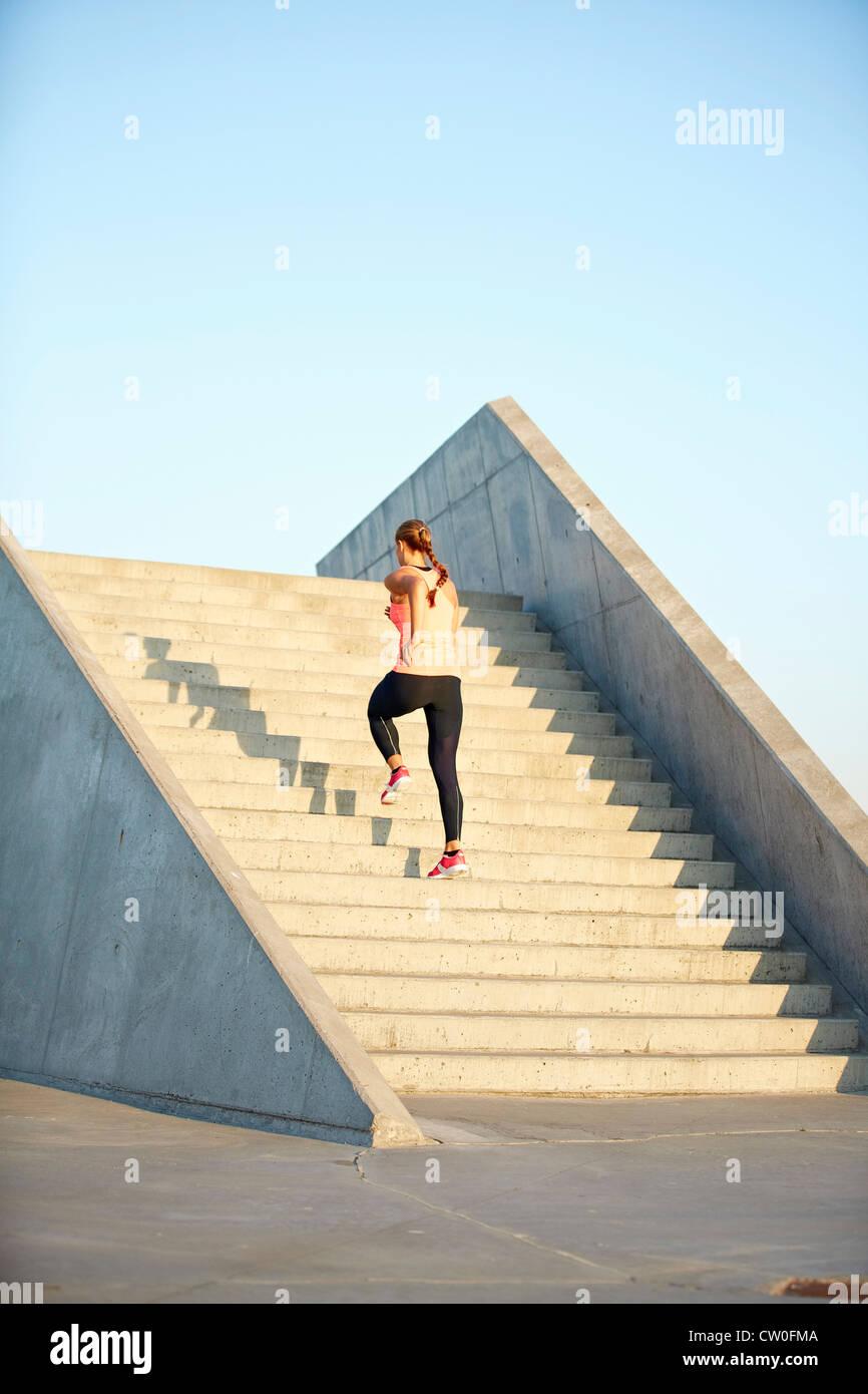 Frau läuft auf Treppe Stockbild