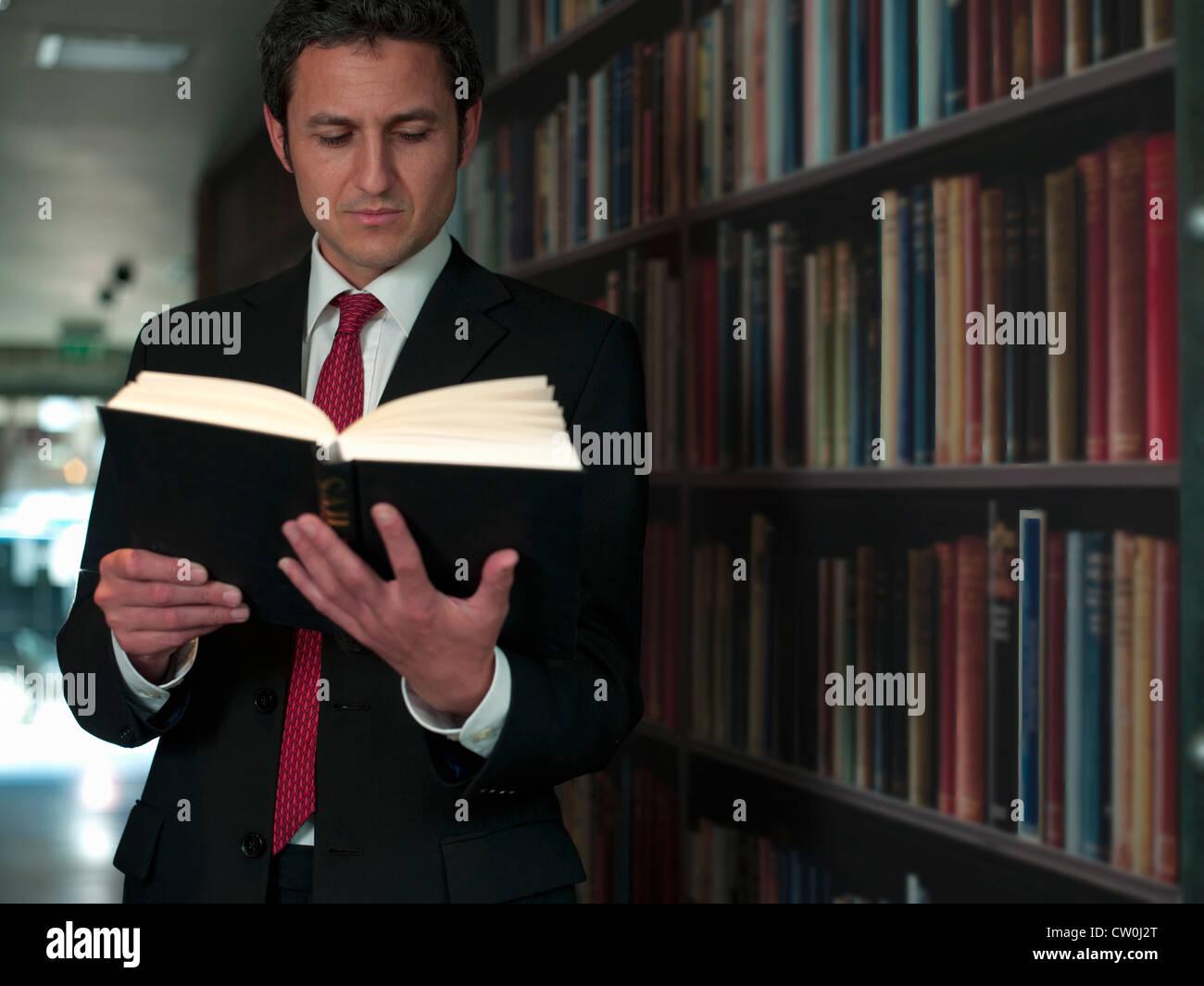 Geschäftsmann Lesebuch in Bibliothek Stockbild