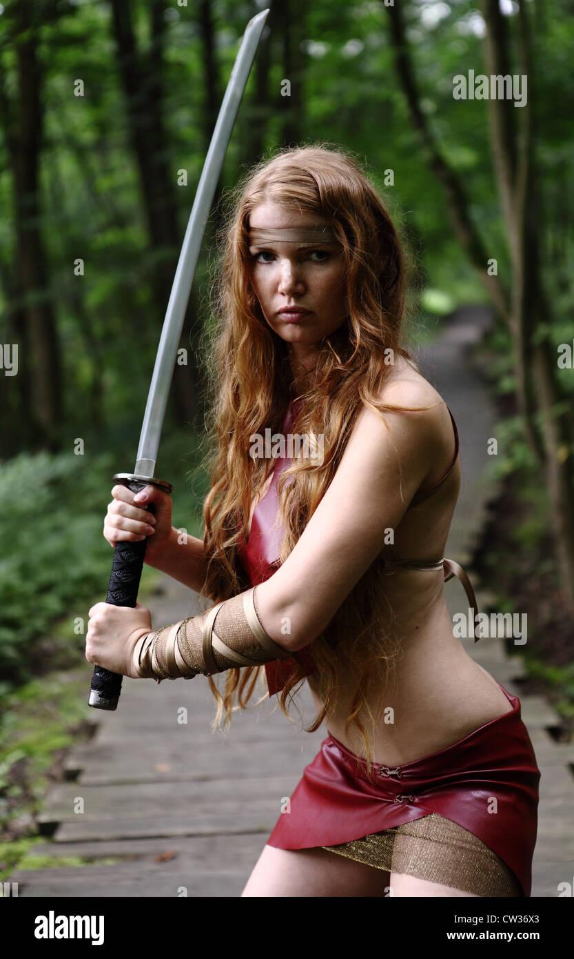 Porträt der jungen Frau mit Schwert im Wald Stockbild