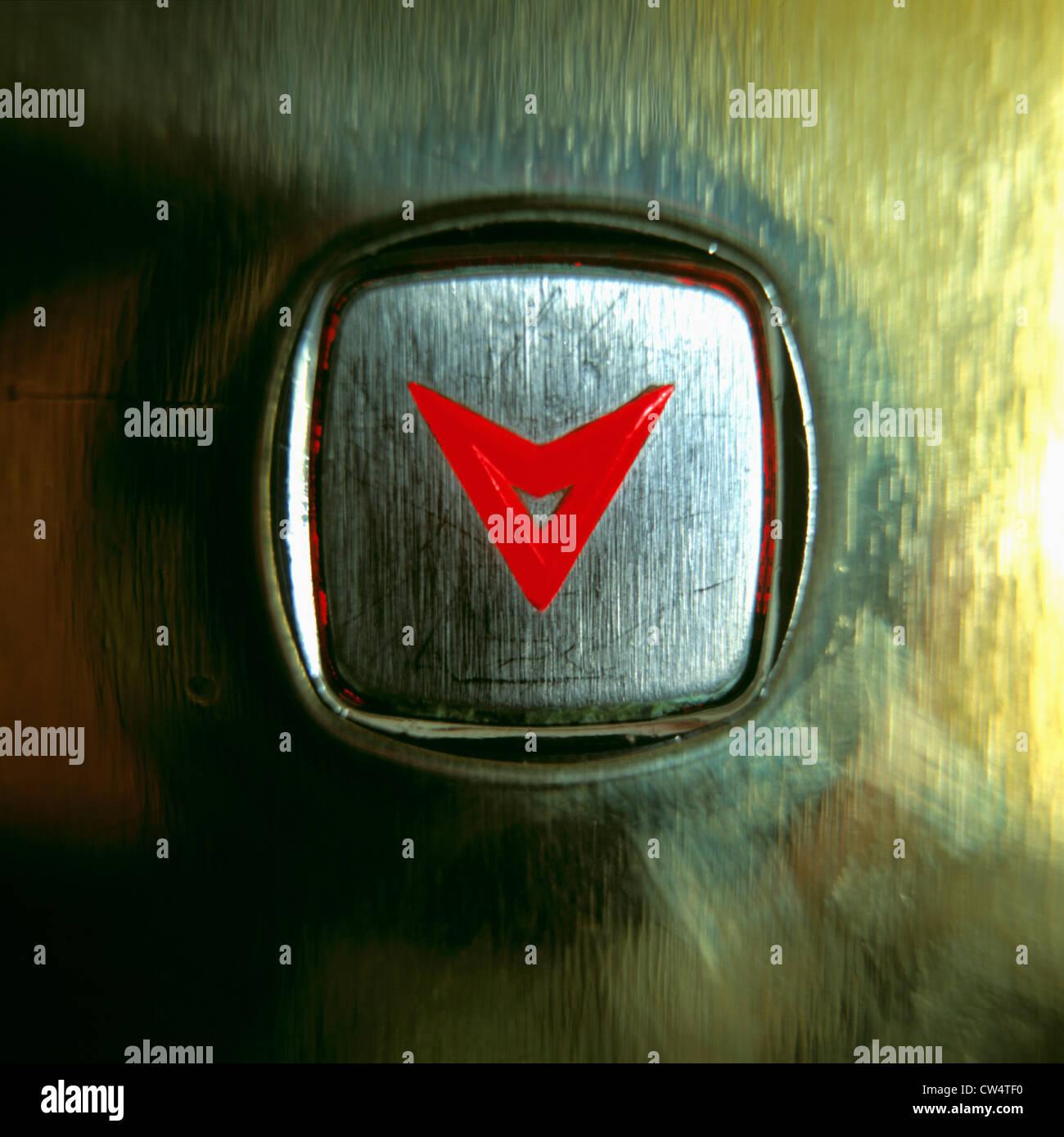 Nahaufnahme von einem Lift-Taste mit einer leuchtenden roten Pfeil nach unten Stockbild