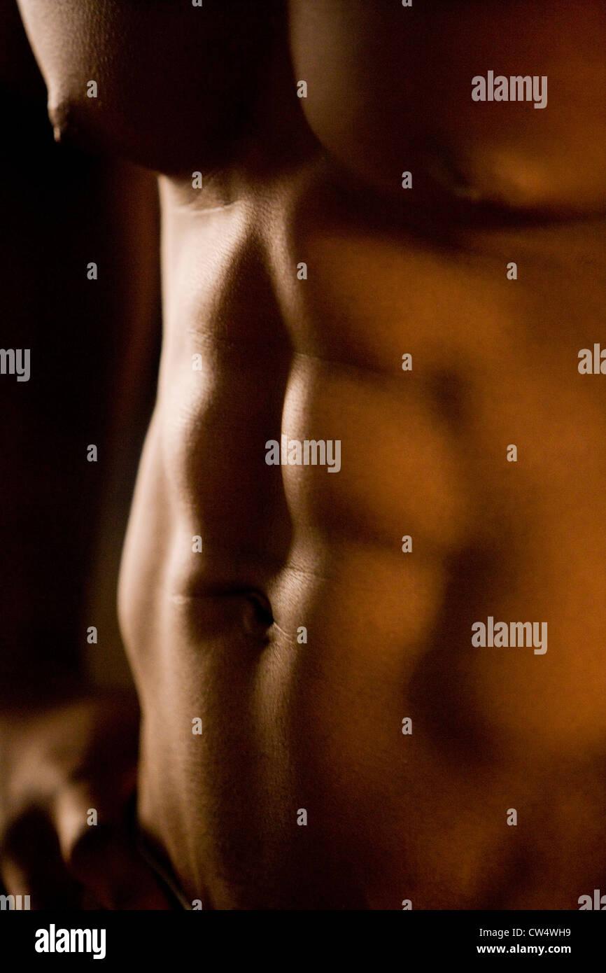 Mittelteil eines shirtless Mannes nach einem Training im Fitnessstudio Stockbild