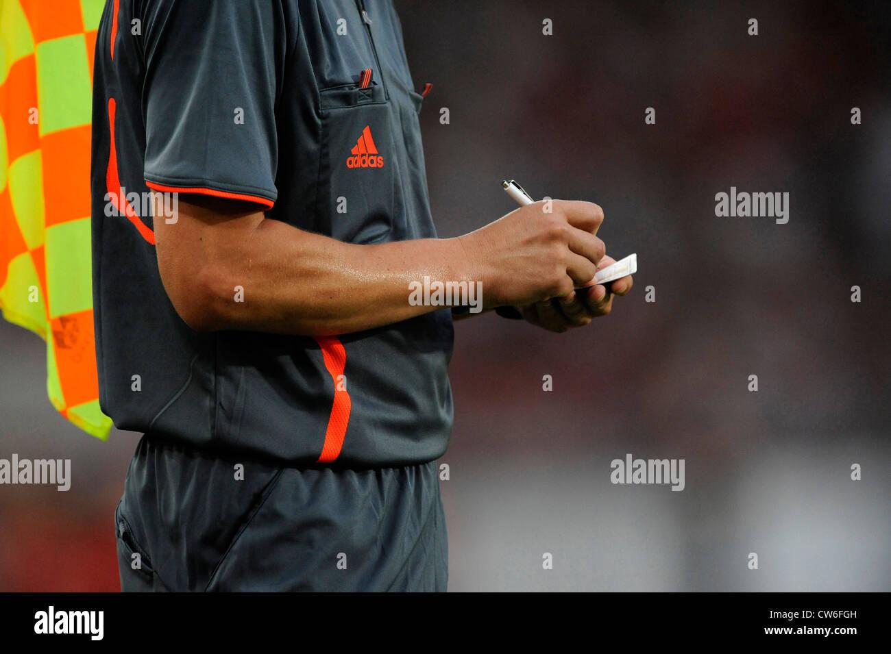 Linienrichter stellt ein Foul in seinem Notizbuch in einem Fußballspiel Stockbild