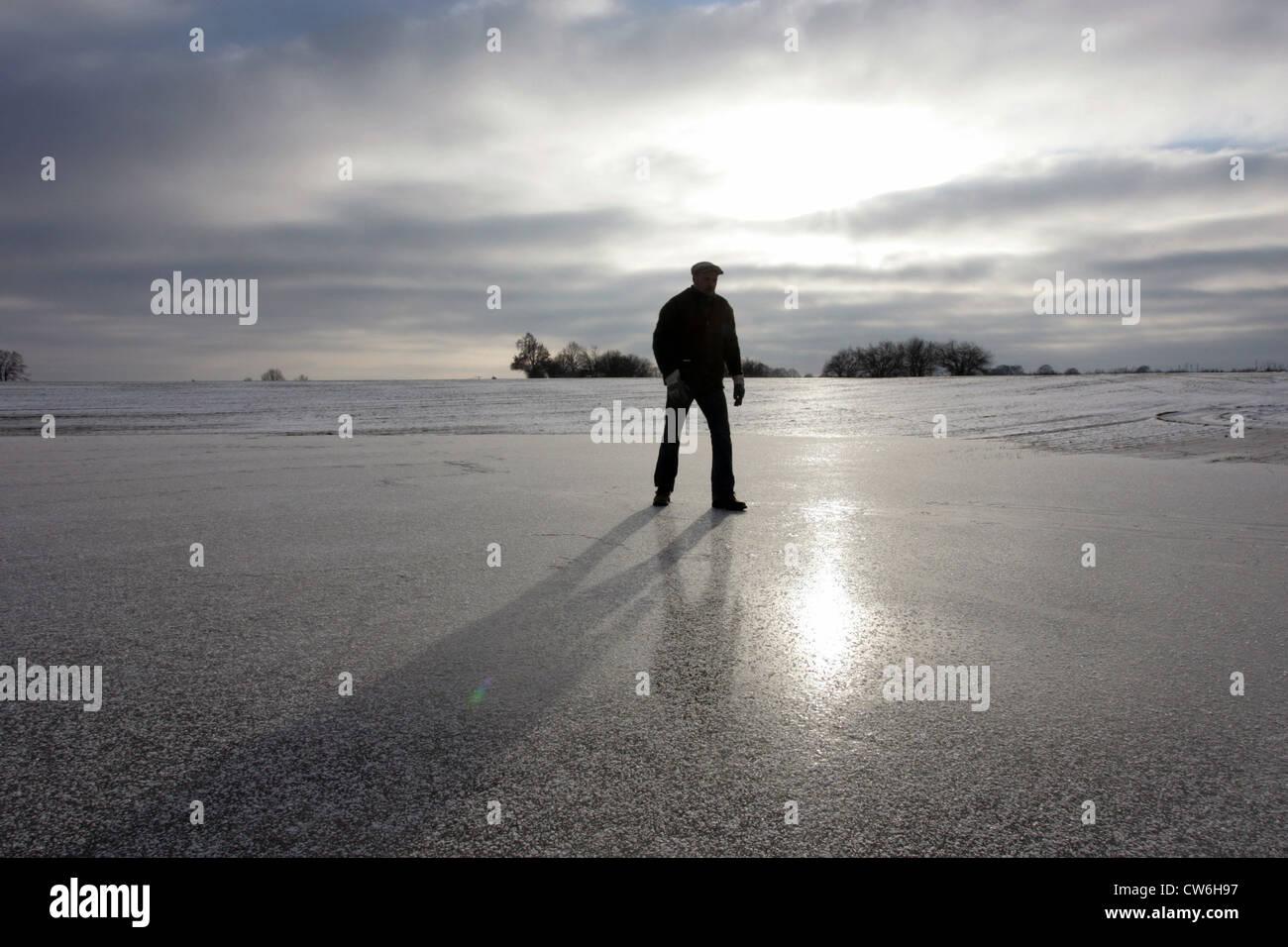 Strahlende Dorf Mann läuft über einen gefrorenen See Stockbild
