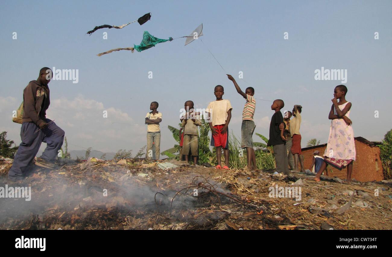 Kinder, die fliegenden Drachen über eine Deponie in den Slums, während Rauch steigt aus der Verbrennung Stockbild