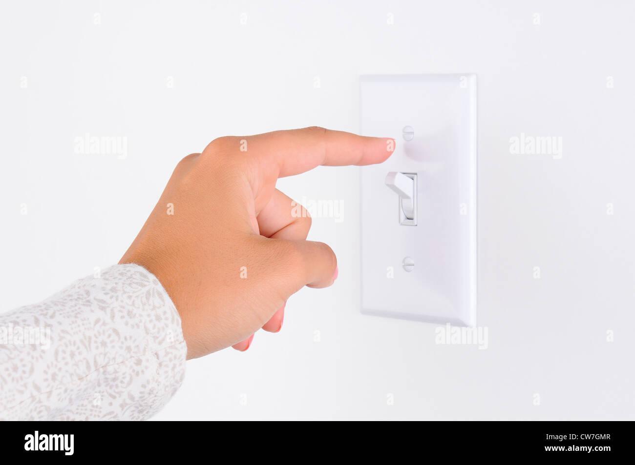 Womans Hand Finger am Lichtschalter, rund um die Lichter ausschalten ...