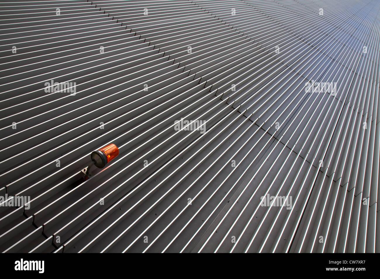 Konvergierende Linien auf einem Wolkenkratzer und eine Alarmleuchte Stockbild