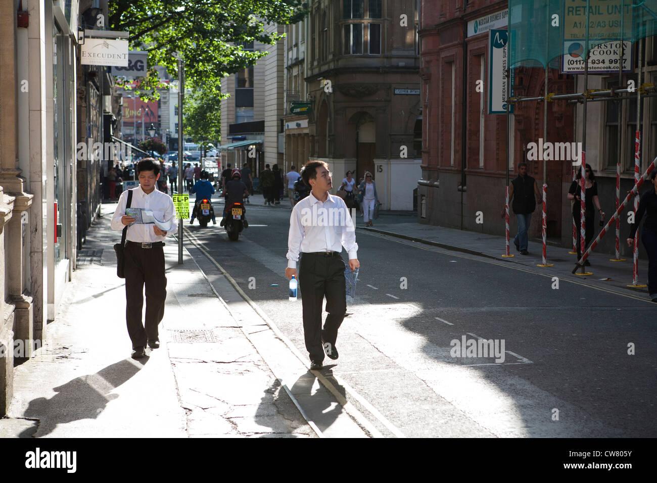Asiatische Touristen in weißen Hemden verloren betrachten Karte in Bristol Stockbild