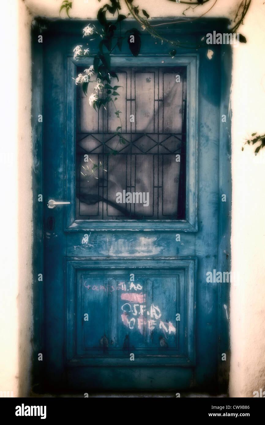 eine alte blaue Holztür mit Graffiti und Gitter Stockbild