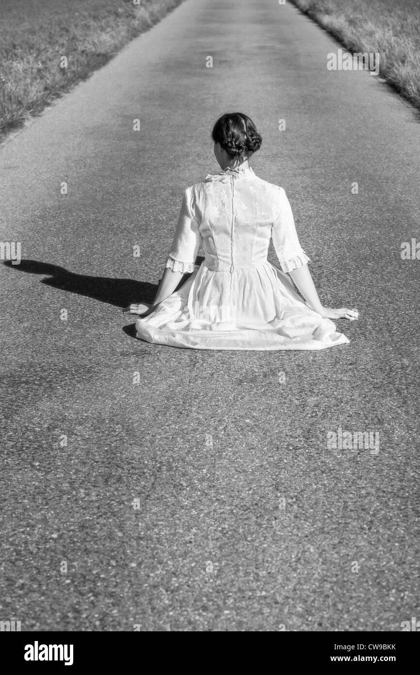 eine Frau in einem viktorianischen Kleid sitzt auf der Straße Stockbild