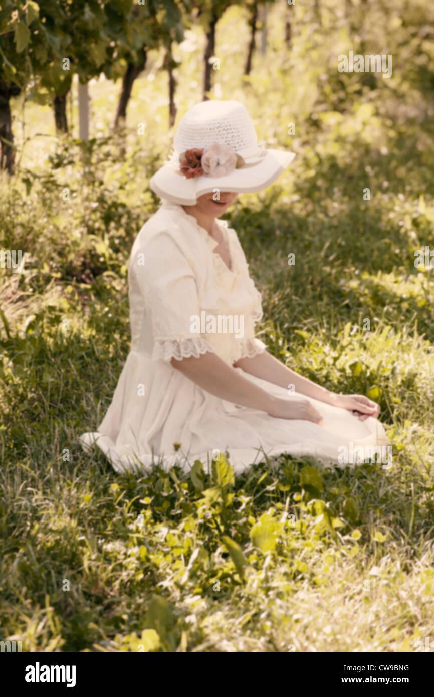 eine Frau in einem weißen viktorianischen Kleid sitzen auf dem Rasen zwischen den Reben Stockfoto