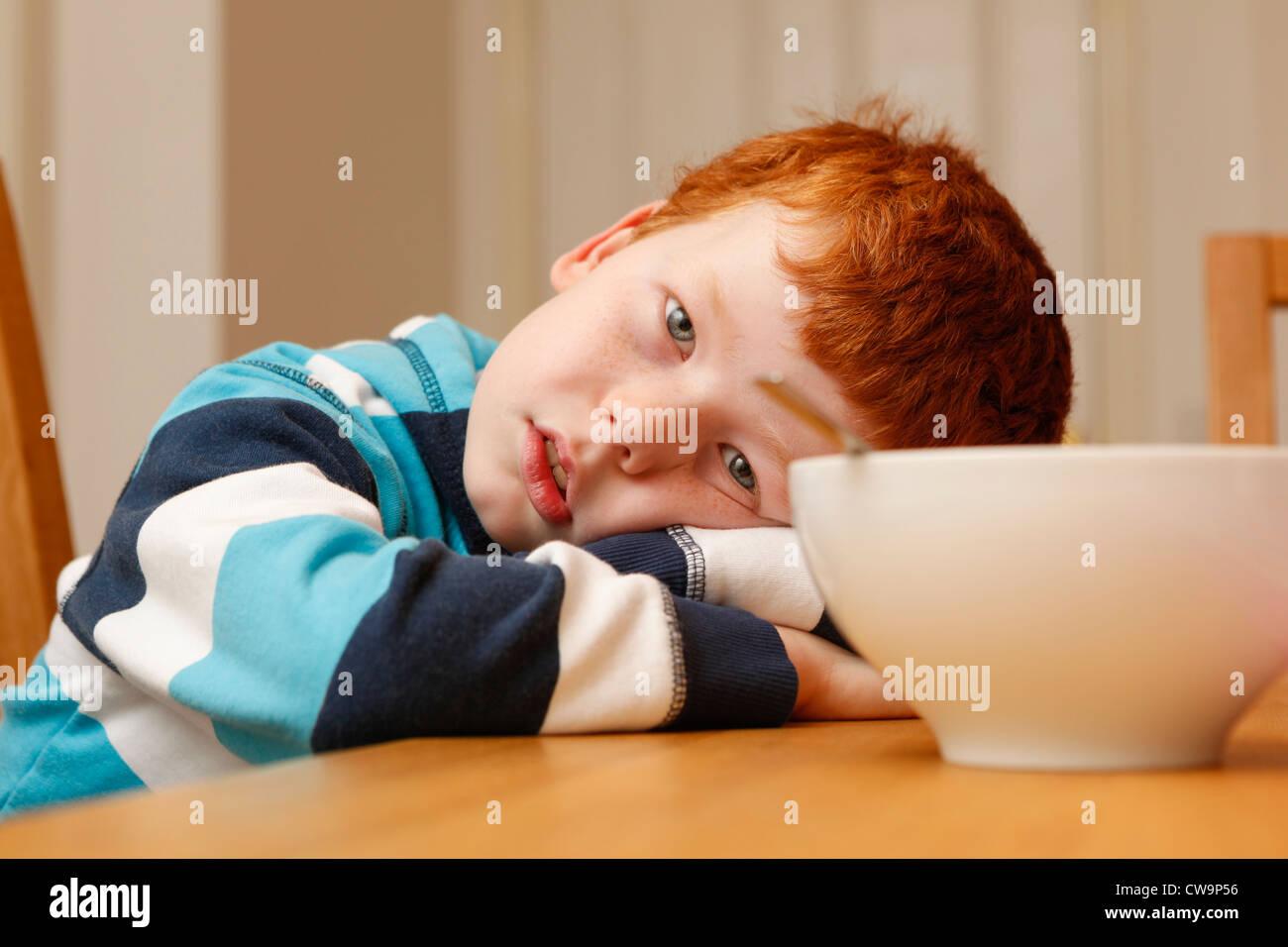 8 Jahre alter Junge müde am Frühstückstisch Stockbild