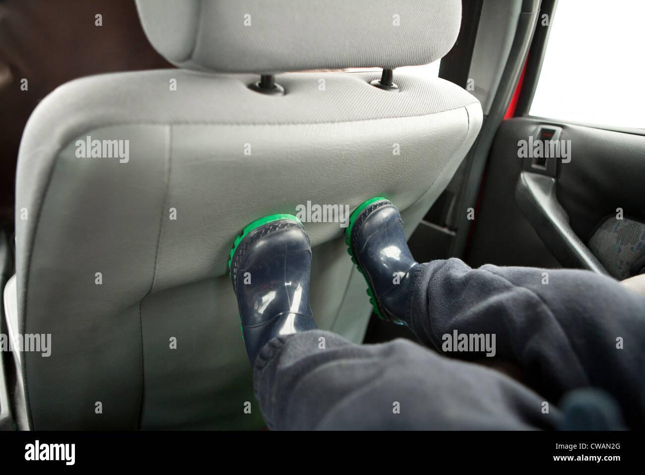 Childs Füße auf der Rückseite des Kindersitzes Stockbild