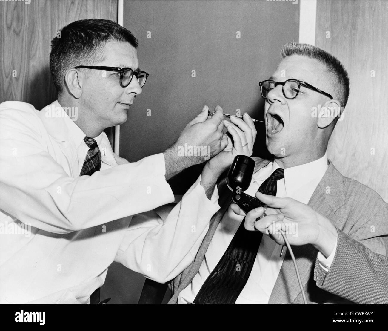 Dr. Harry L. Williams spritzt LSD aus einer Spritze in den Mund des Carl Curt Pfeiffer, M.D., Ph.d. (1908-1988) Stockbild