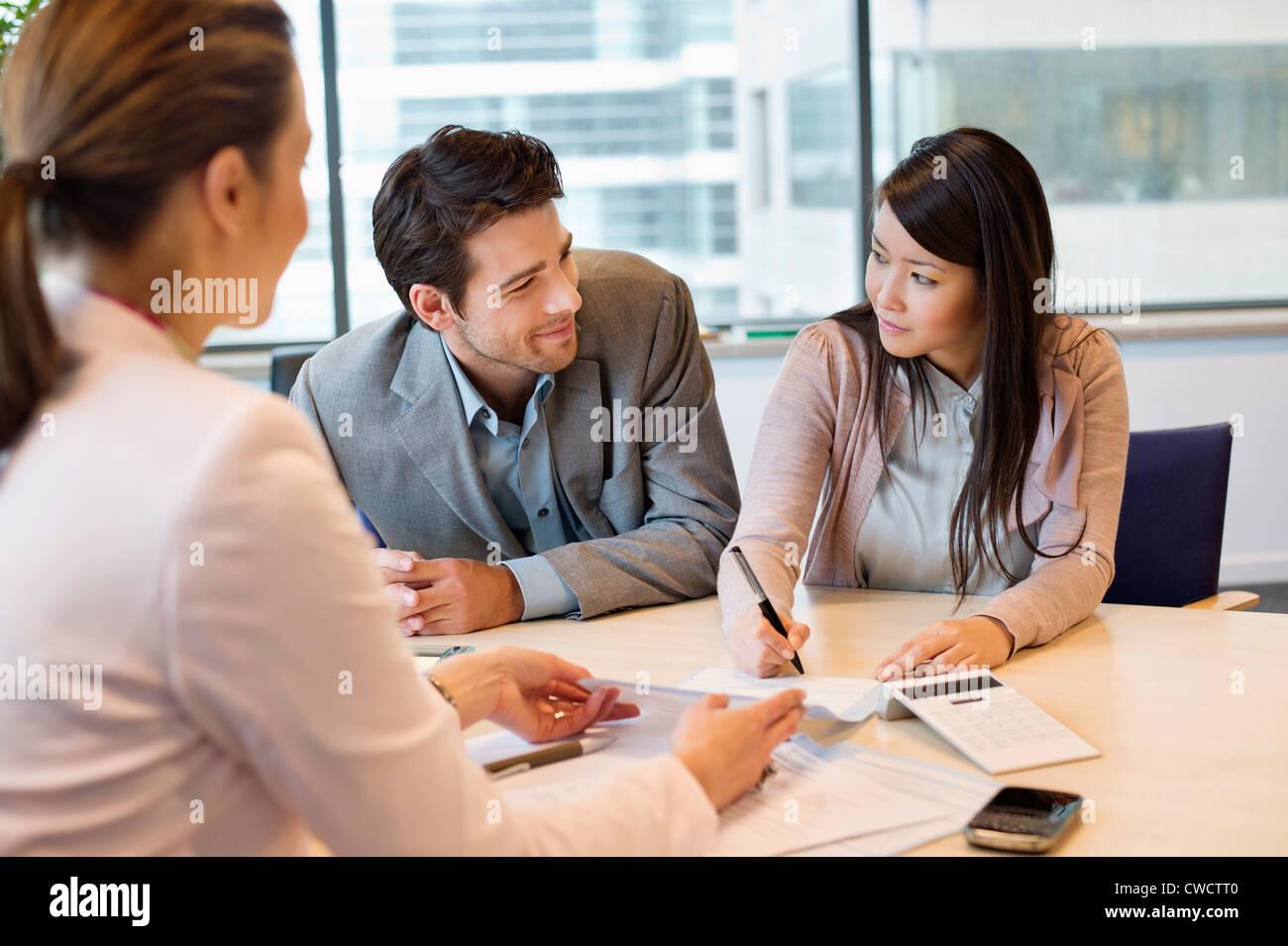 Paar Signieren von Dokumenten mit Immobilienmakler Stockbild