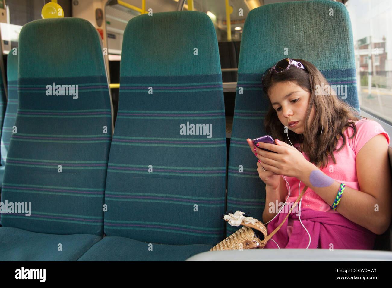 Junges Mädchen hört Musik auf die öffentlichen Verkehrsmittel, London, England Stockbild