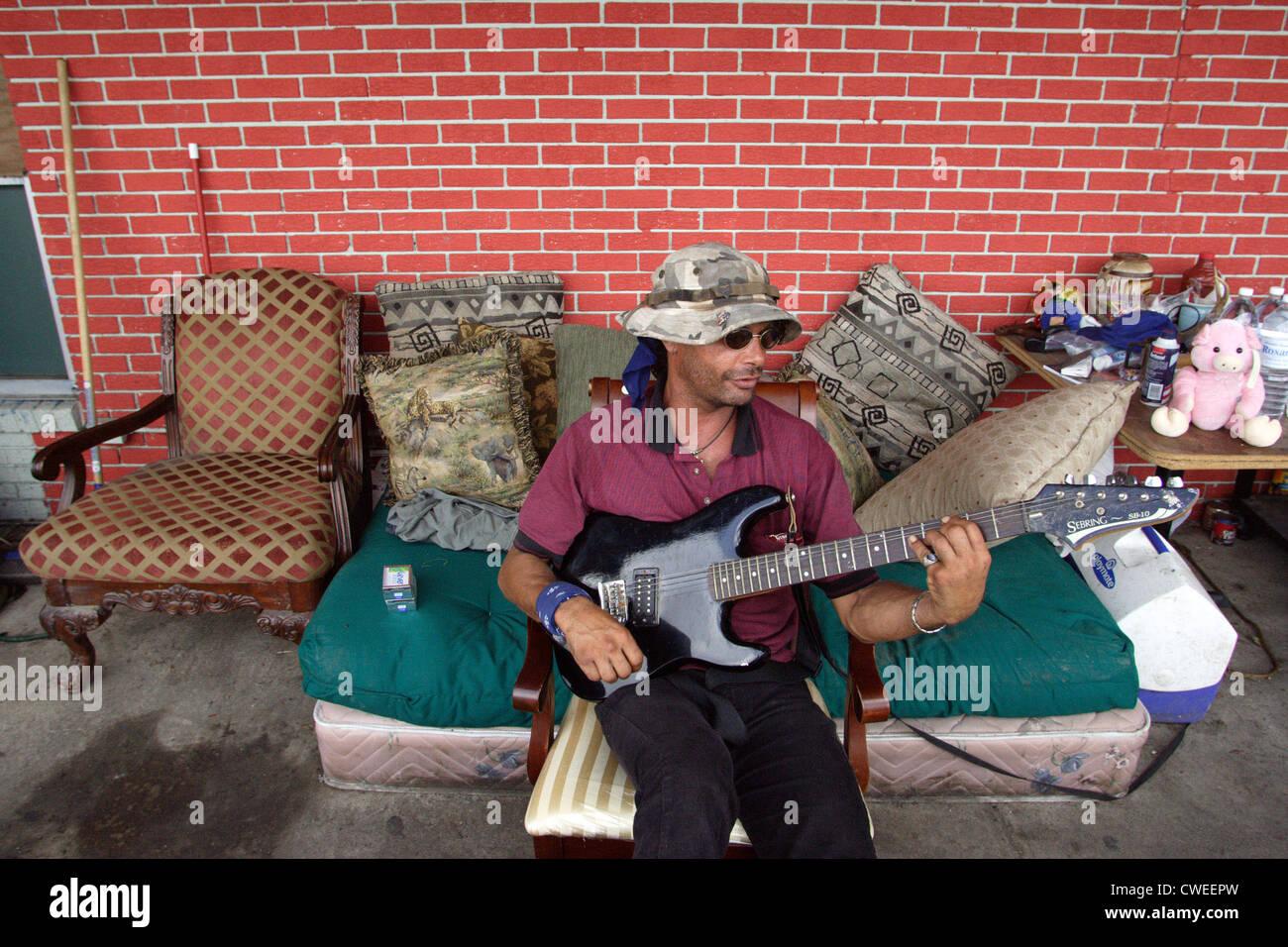Mann, der seine e-Gitarre spielt nach dem Hurrikan Katrina Stockbild