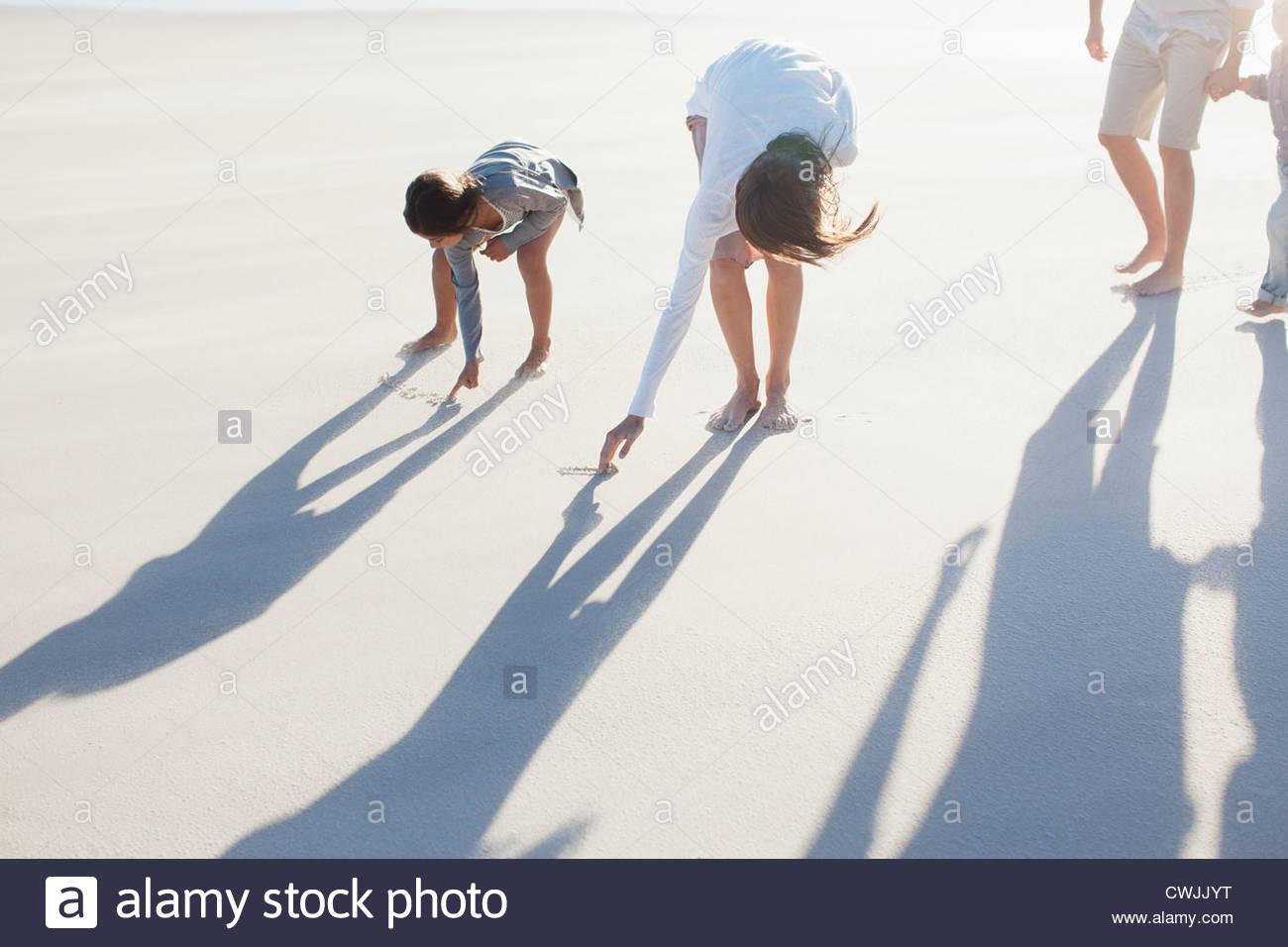 Familie schreiben in Sand am Strand Stockbild