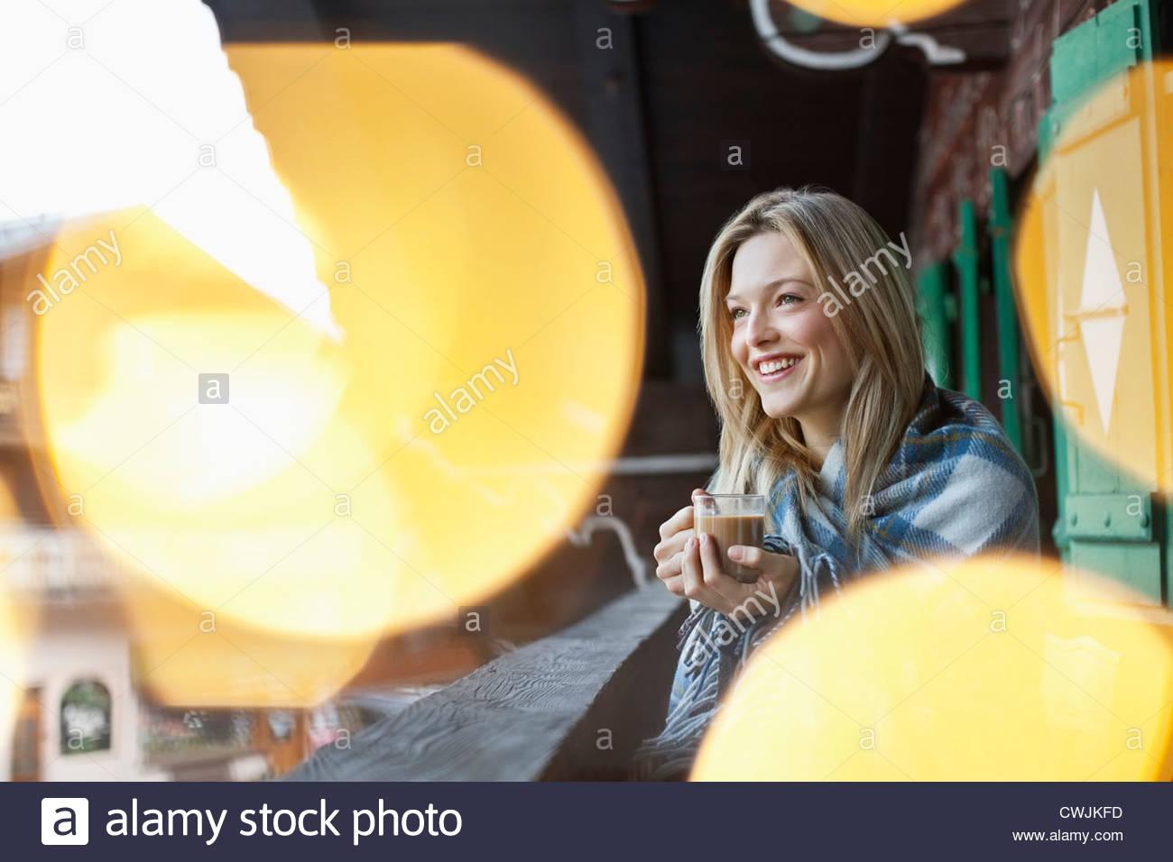 Lächelnde Frau eingewickelt in eine Decke und Kaffee auf der Veranda der Hütte Stockbild
