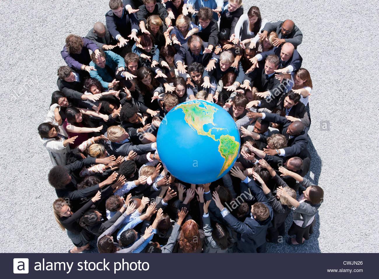 Menge von Geschäftsleuten im Huddle erreichen für globe Stockbild
