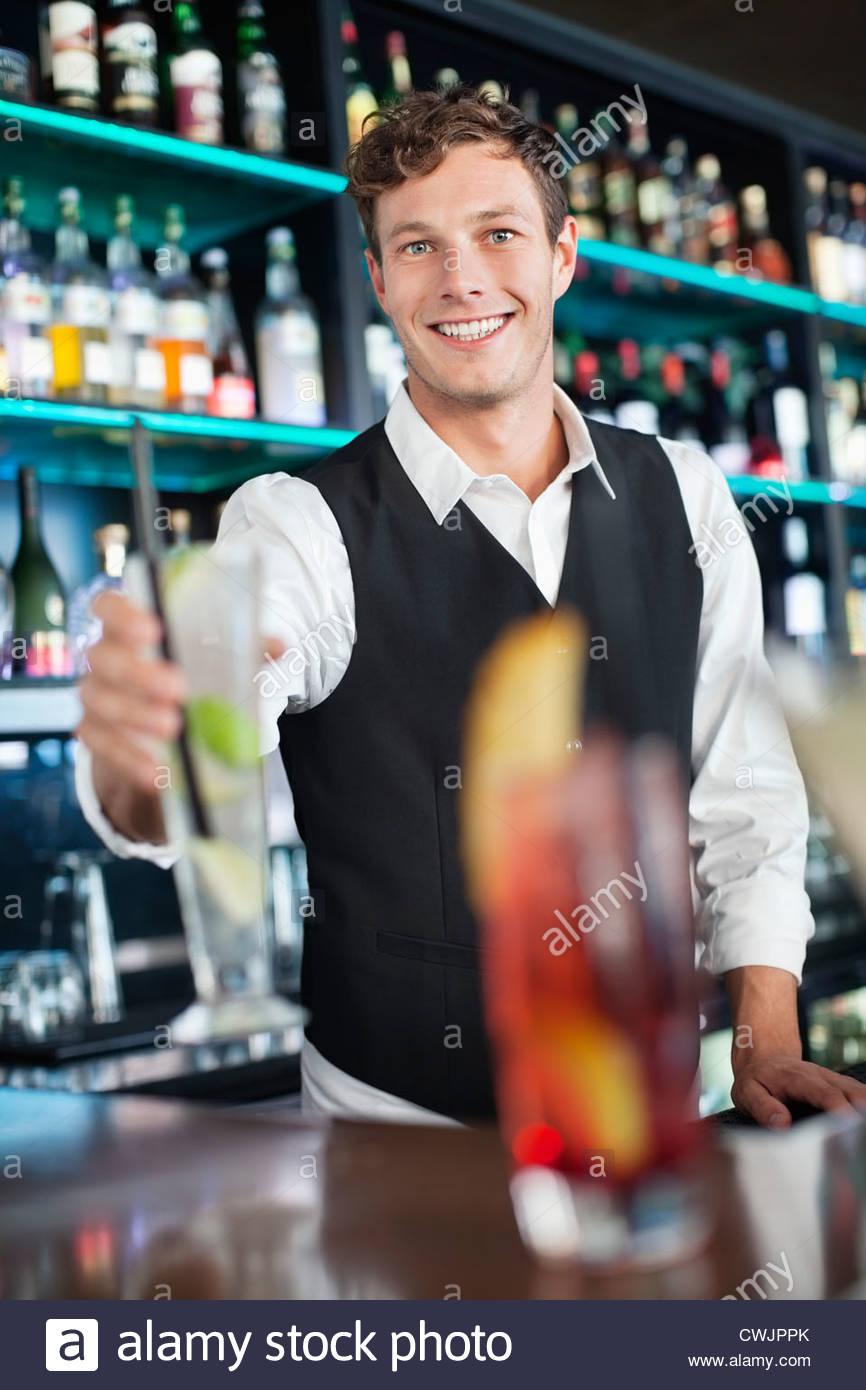 Porträt von lächelnden Barkeeper cocktail halten Stockbild