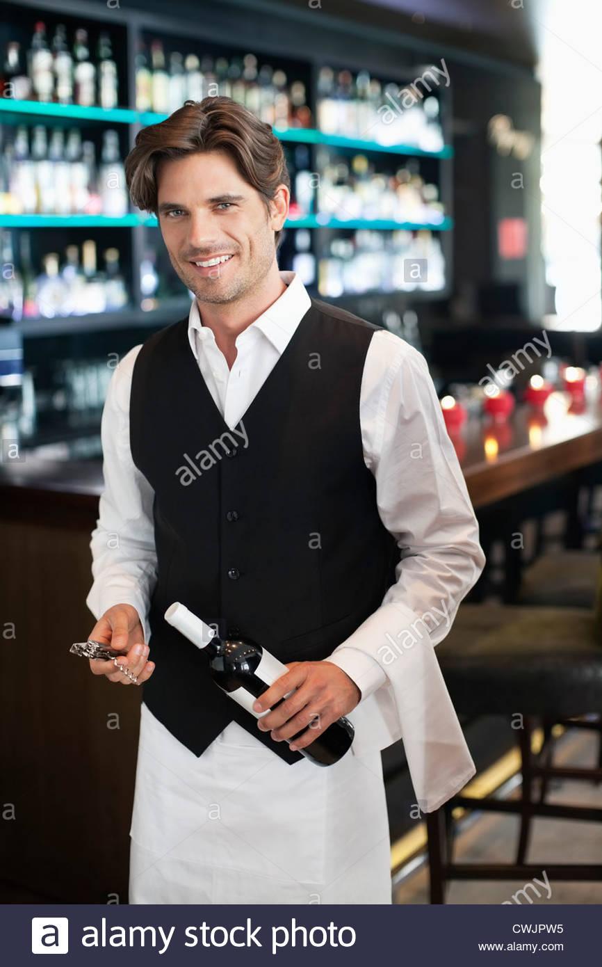 Porträt des Lächelns Sommelier mit Flasche Wein in der Bar Stockbild