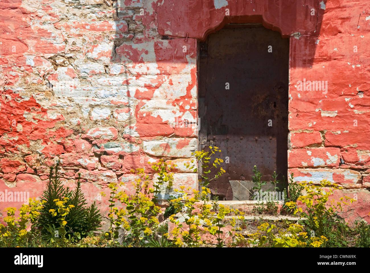 Bunte Fassade ein altes Steinhaus mit verwitterten Metalltür auf Pilion Halbinsel, Thessalien, Griechenland Stockbild