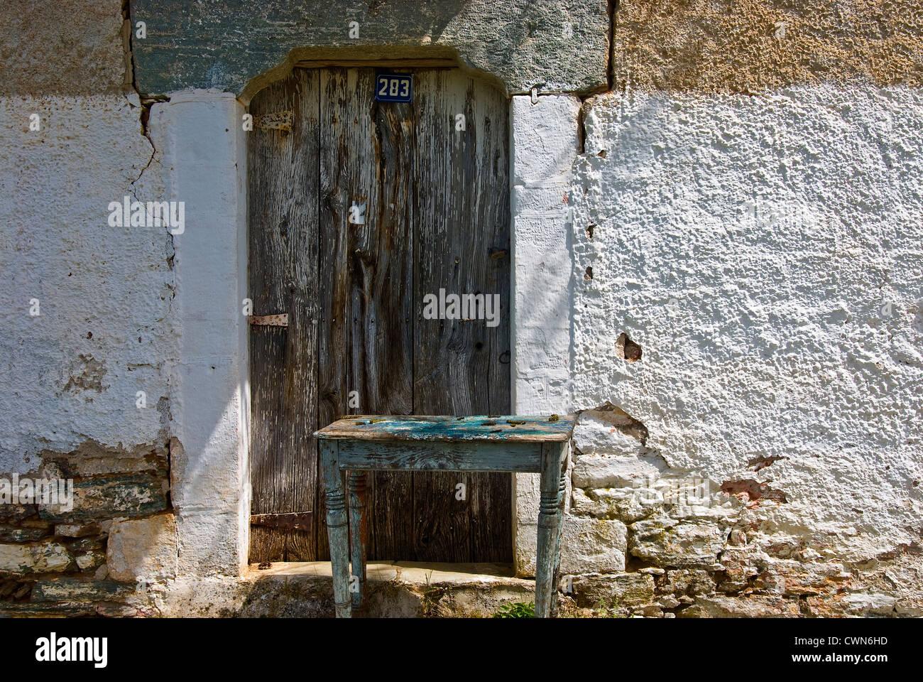 Fassade von einer alten Steinhaus mit verwitterten Holztüre auf Pilion Halbinsel, Thessalien, Griechenland Stockbild
