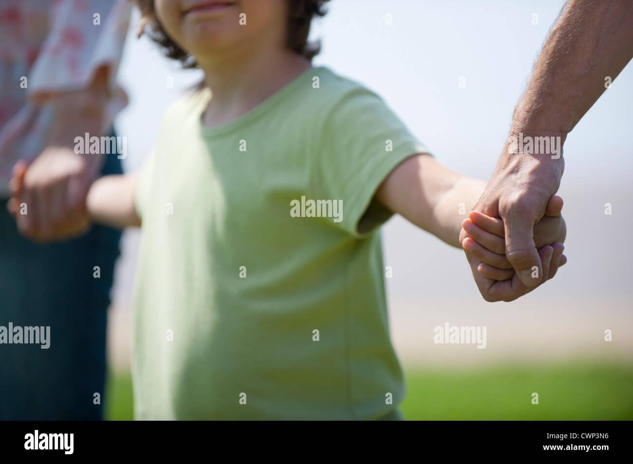 Junge, die Hand in Hand mit Eltern, beschnitten Stockbild
