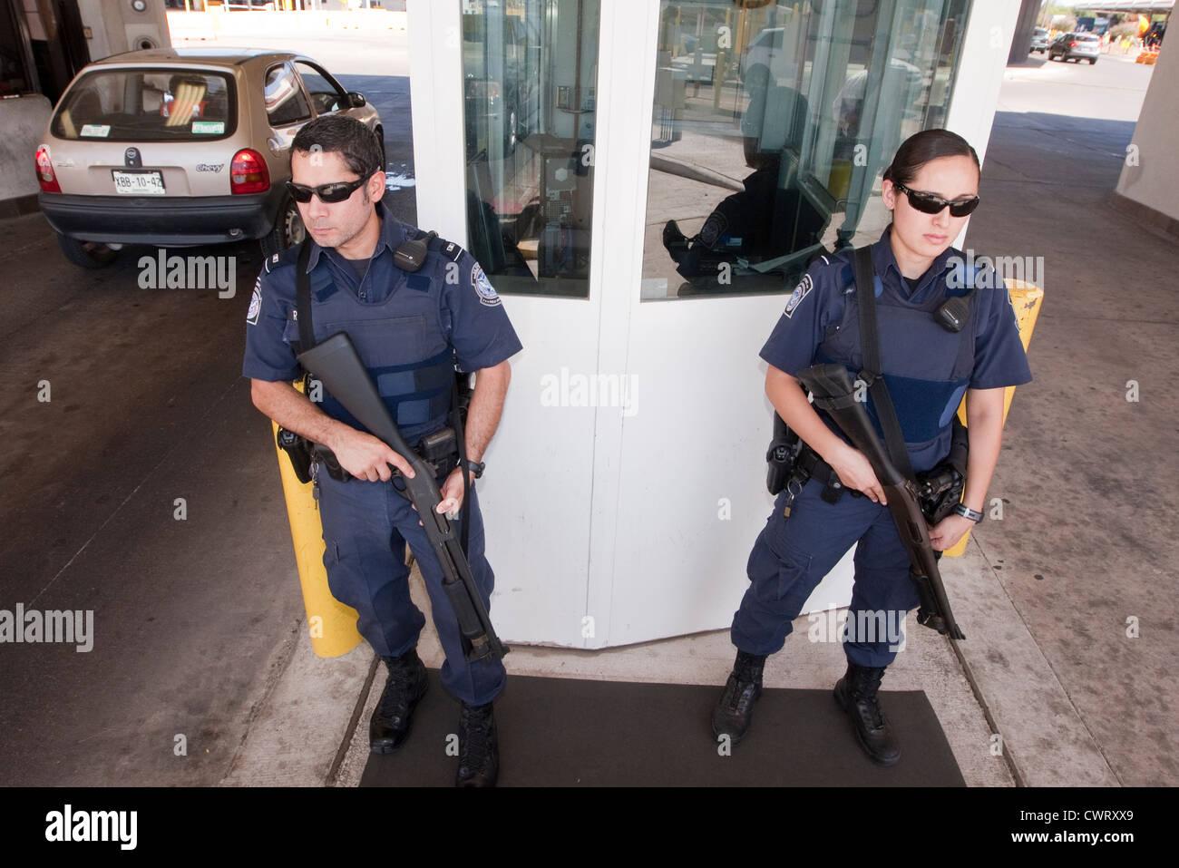 Wachen Sie männliche und weibliche Offiziere, mit Gewehren auf die internationale Brücke Laredo, Texas. Stockbild