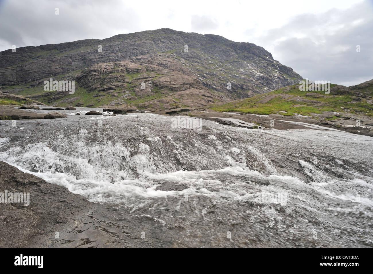 Schnell fließenden Fluss rinnt aus Bergen Stockbild