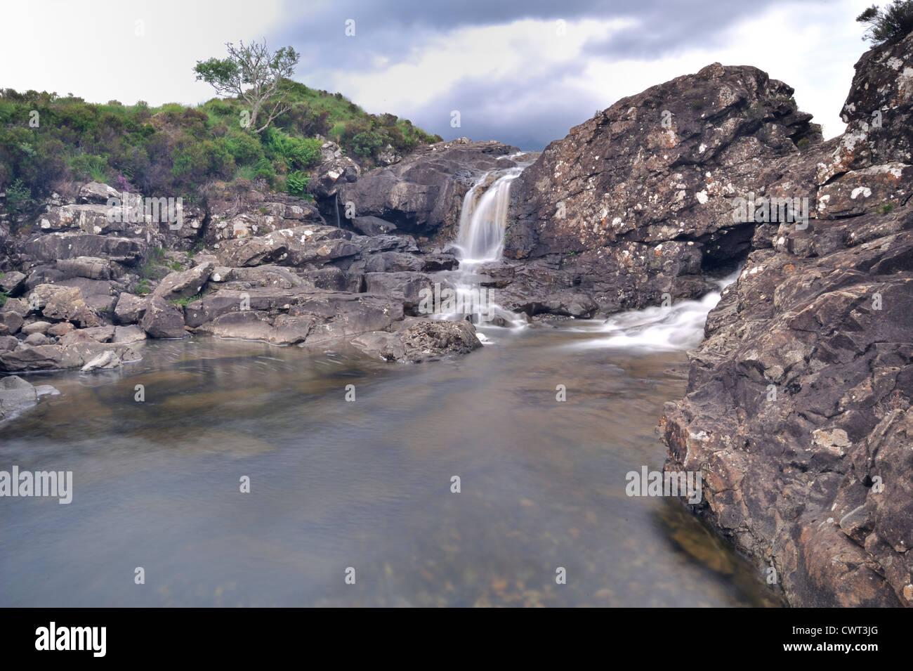 Schnell fließenden Fluss hautnah mit Wasserfall im Hintergrund Stockbild