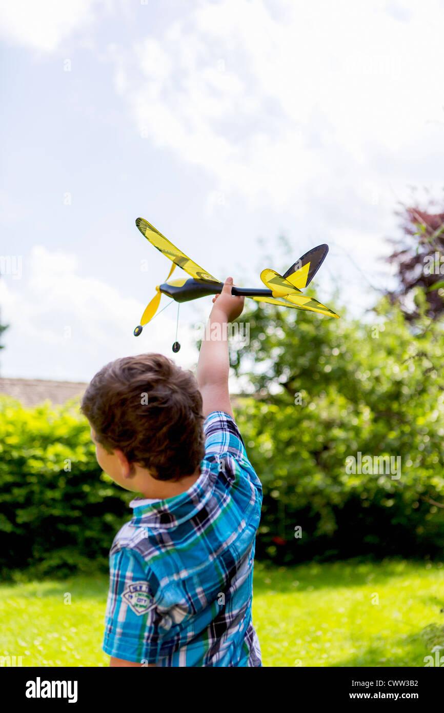 Jungen spielen mit Spielzeugflugzeug im freien Stockbild