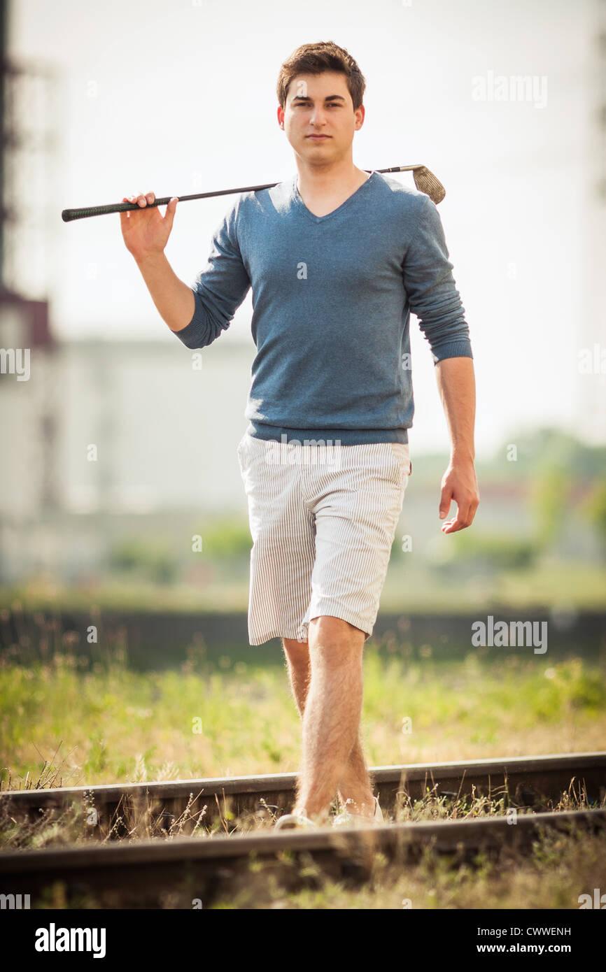 Mann trägt Golfclub auf Schienen Stockbild